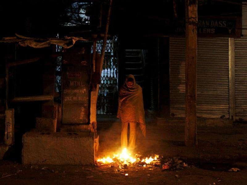 A homeless man keeps himself warm near a bonfire on a pavement in New Delhi. AP Photo