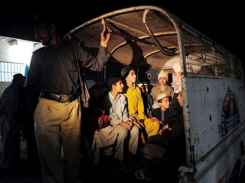 Rescued Pakistani students sit in a police vehicle following a police raid on Madrassa Zakarya in Karachi. Pakistani police rescued 45 students found chained in the basement during a raid late on an Islamic seminary in the southern port city of Karachi, police said. Some Islamic schools in Pakistan are accused of training militants and supporting violent extremist groups, with some dispatching fighters to neighbouring Afghanistan. AFP PHOTO / ASIF HASSAN