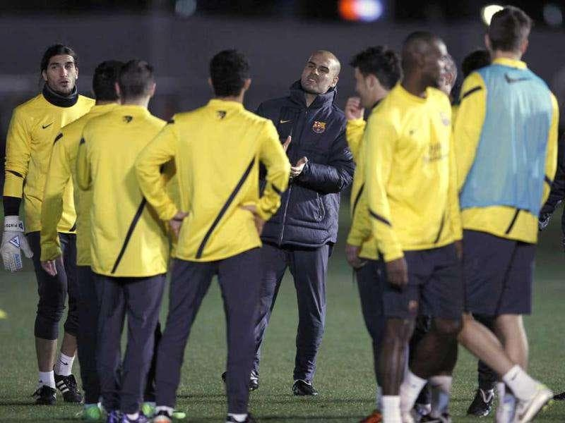 Barcelona's coach Pep Guardiola (C) speaks to his team during a practice session for their upcoming FIFA Club World Cup soccer match against Qatar's Al Sadd in Yokohama, south of Tokyo.