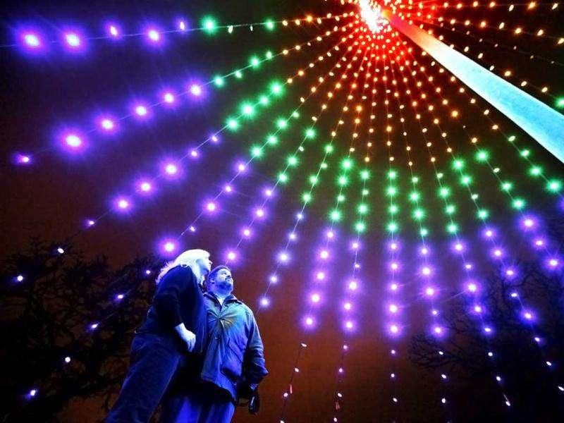 A couple enjoying an up-close view of a seasonal display at the Holiday Fantasy of Lights in Olin-Turville Park, Madison, Wis. (AP/Wisconsin State Journal, John Hart)