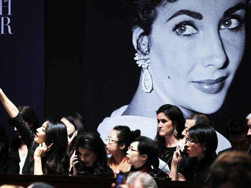 A phone bidder signals her bid near an image of Elizabeth Taylor during an auction of the late actress' jewelry, clothing, art and memorabilia at Christie's Auction house in New York. (Reuters/Carlo Allegri)