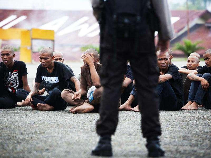 A policeman guards a group of detained Indonesian punks, arrested at a punk rock concert, at a police school in Aceh Besar in Aceh province. AFP Photo