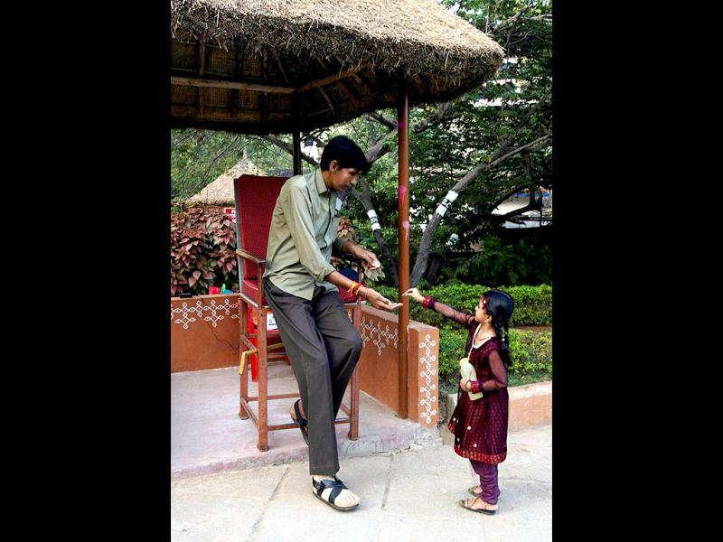 A girl gives money to Polipaka Gattaiah, who stands at seven-and-a-half feet and claims to be the tallest man in India, at the arts and crafts centre in Hyderabad. Gattaiah entertains people who visit the centre and is paid Rs 6500 a month by the state tourism department. Reuters Photo