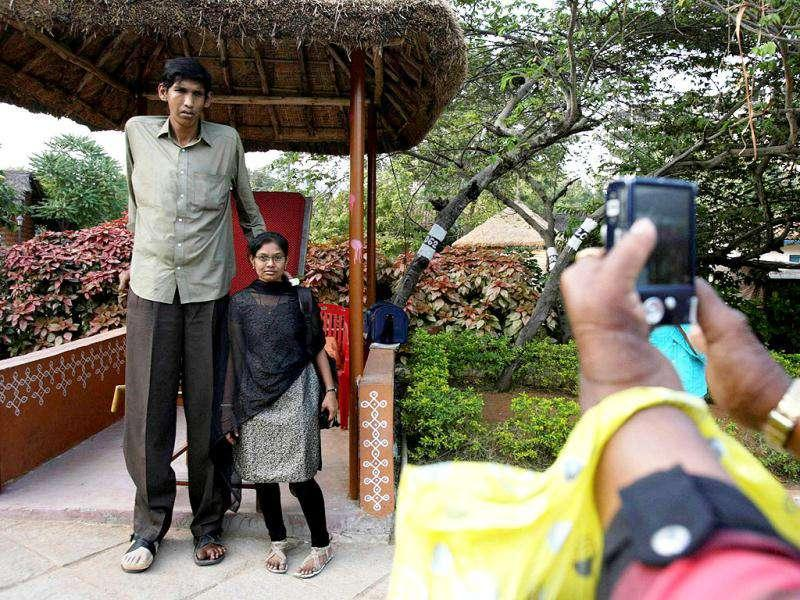 A visitor poses with Polipaka Gattaiah, who stands at seven-and-a-half feet and claims to be the tallest man in India, at the arts and crafts centre in Hyderabad. Reuters Photo