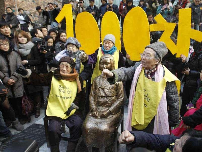 A former South Korean comfort woman Kil Un-ock, right, who was forced to serve for the Japanese Army as a sexual slave during World War II, shouts slogans with other comfort women next to the statue symbolizing a wartime sex slave during their 1,000th rally to demand an official apology and compensation from the Japanese government in Seoul. (AP Photo/ Lee Jin-man)