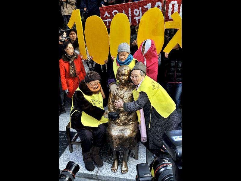 South Korean elderly women (yellow vests), who served as sex slaves for Japanese soldiers during World War II, hug the statue of a South Korean teenage girl in traditional costume called the