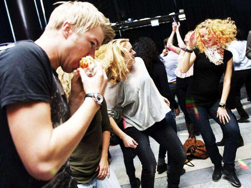 A man eats a sandwich while dancing with his friends during one of the Lunch Beat sessions held at the Culture House in central Stockholm. The Lunch Beat is a growing movement in Sweden, mixing a work break with a bit of disco fever. AFP Photo