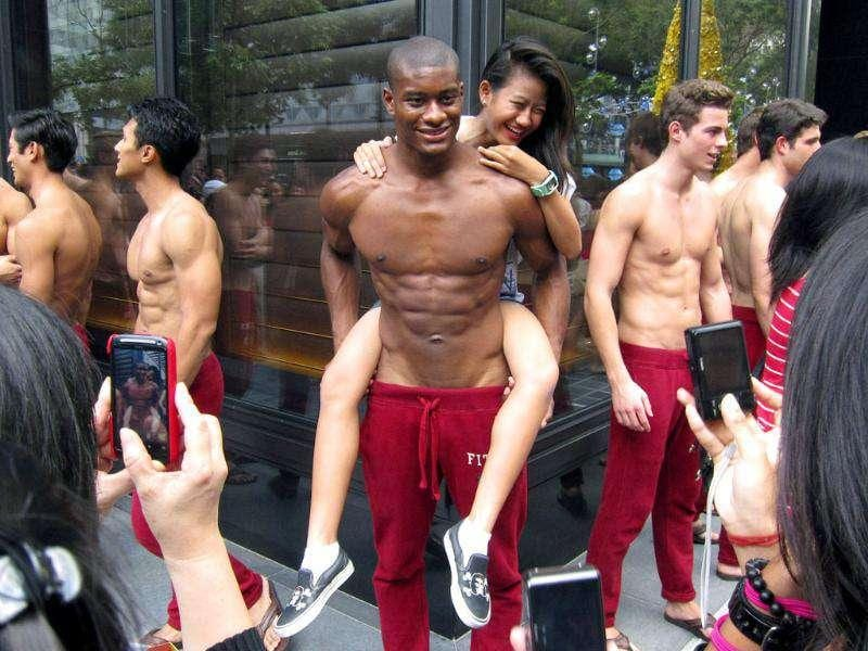 A woman poses with a shirtless model outside a department store in Singapore's Orchard Road shopping district. Shirtless men clad in red sweatpants have been lining up for days as part of an advertising gimmick revealing not just muscle but also a gradual unpeeling of the city state's puritanical ways. Reuters Photo
