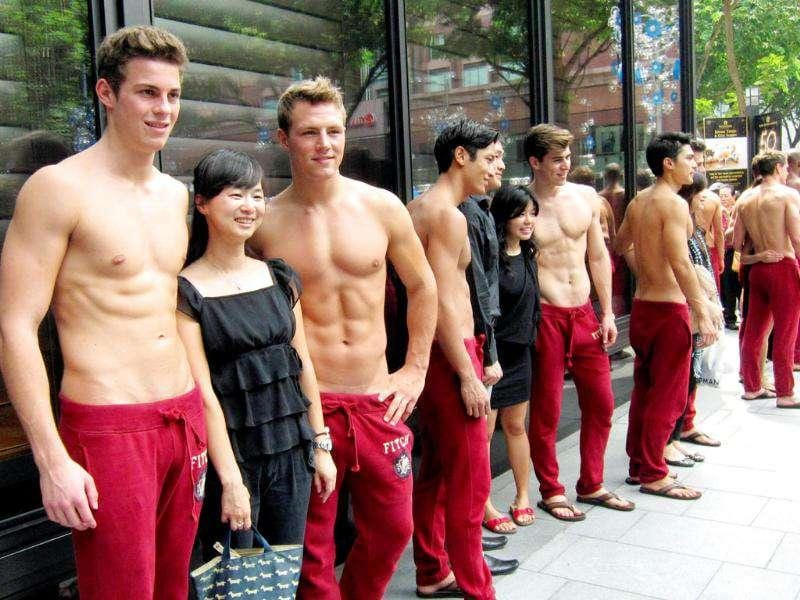 People pose for photographs with shirtless models outside a department store in Singapore's Orchard Road shopping district. Shirtless men clad in red sweatpants have been lining up for days as part of an advertising gimmick revealing not just muscle but also a gradual unpeeling of the city state's puritanical ways. Reuters Photo