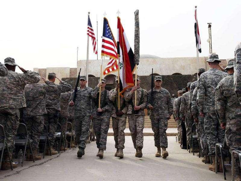 Members of the US military retire its ceremonial flags signifying the end of their presence in Iraq at the Baghdad Diplomatic Support Center in Baghdad. (Reuters/Shannon Stapleton)