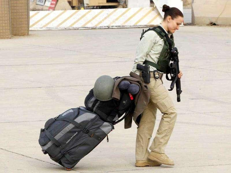 A member of US security officer pulls her luggage while waiting to depart from Iraq, at the former US Sather Air Base near Baghdad. (Reuters/Mohammed Ameen)