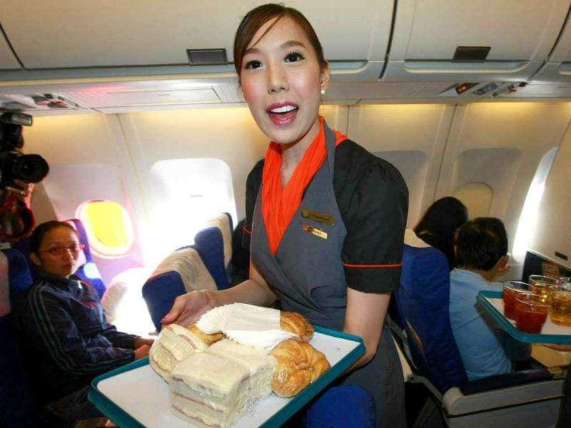 Thai transsexual flight attendant Phuntakarn Sringern serves food during a flight in Thailand. AP Photo/Apichart Weerawong.