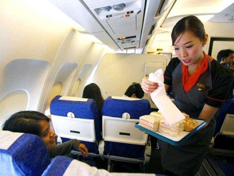 PC Air transsexual flight attendant Chayathisa Nakmai, 24, serves passengers on PC Air's aircraft. Reuters/Chaiwat Subprasom.