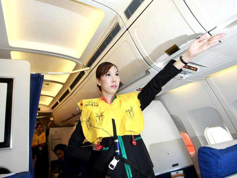 Thai transsexual flight attendant Chayathisa Nakmai introduces in-flight safety during a flight in Thailand. AP Photo/Apichart Weerawong.