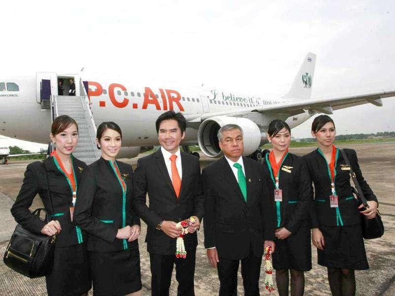 PC Air transsexual flight attendants (L to R): Chayathisa Nakmai, 24, Dissanai Chitpraphachin, 24, Peter Chan, president of PC Air, Chatwiwat Klamkomol, chairman of PC Air, Nathatai Sukkaset, 26, and Phuntakarn Sringern, 24, pose for photographers in front of a PC Air plane at Surat Thani Airport. Reuters/Chaiwat Subprasom.