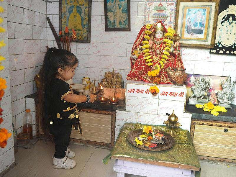 Jyoti Amge, 18, who stands at 62.8cm (24.7 inches), offers prayers near her residence in Nagpur. Amge was officially announced by the Guinness World Records the world's