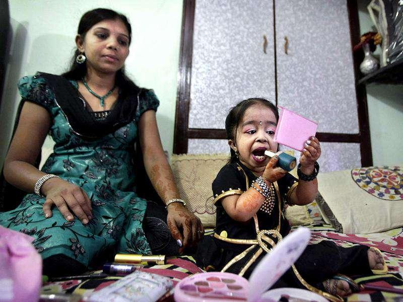 Jyoti Amge, 18, who stands at 62.8cm (24.7 inches), puts on lipstick while her sister Archna looks on as she prepares for a press conference with Guinness World Records in Nagpur.