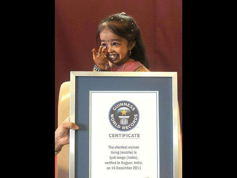 Jyoti Amge, 18, wipes a tear after receiving an official certificate from Guinness World Records in Nagpur on December 16, 2011. Amge was officially announced by the Guinness World Records on December 16 the world's