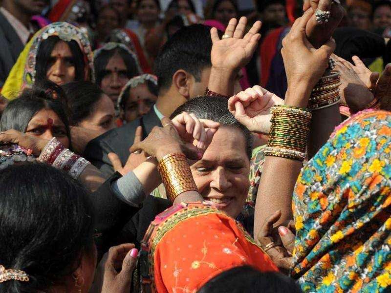 UPA chairperson and Congress party president Sonia Gandhi (C) dances with tribal women during a convention of Tribal women in New Delhi. (AFP Photo/Prakash Singh)