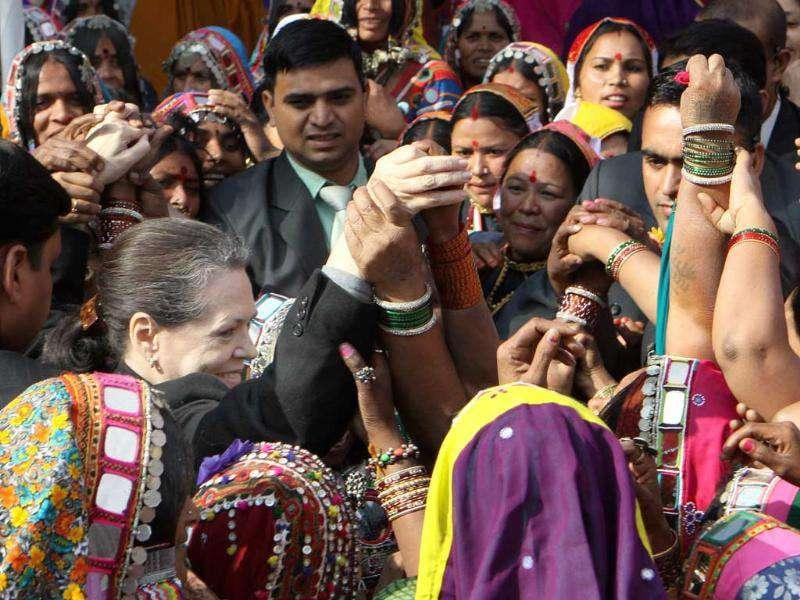 UPA chairperson and Congress party president Sonia Gandhi (C) dances with tribal women during a convention of tribal women in New Delhi. (HT Photo/Sonu Mehta)