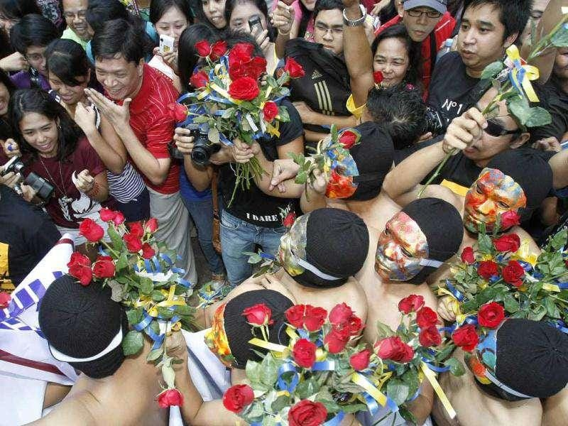 Members of the Alpha Phi Omega fraternity squeeze through a crowd of shrieking students as they run naked along Palma Hall of the University of the Philippines campus in Manila. More than 30 members ran naked in the annual 'Oblation Run' with this year's theme of saving the country's rivers and increase awareness on climate change. (AP/Bullit Marquez)