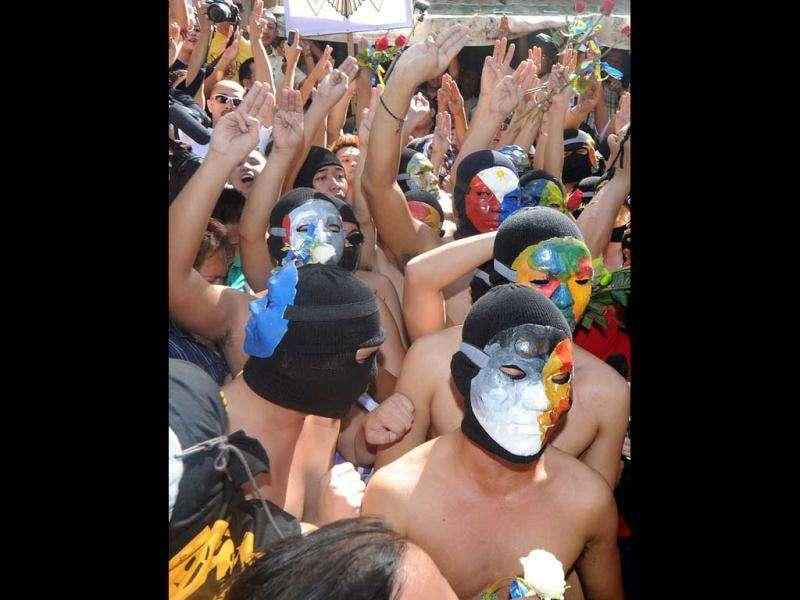 Nude members of a university fraternity wearing masks walk through a crowd of fellow students during the traditional 'Oblation Run' at the University of the Philipppines campus in suburban Manila. The nude run is used each year to draw attention to the major issues of the day in the Philippines. (AFP/Noel Celis)