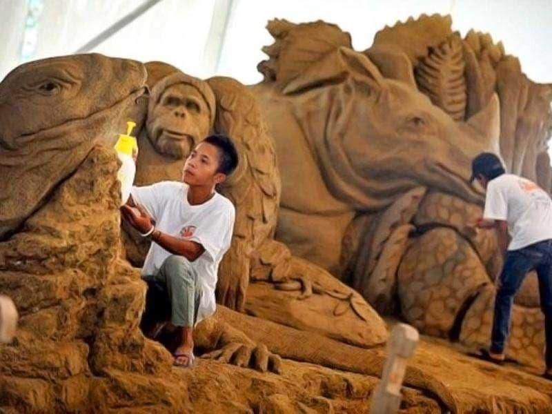 Workers spray water and clean the sand sculptures featuring world famous figures and landmarks during the 1st Sand Sculptures Festival at cultural park in Sentul outside of Jakarta, Indonesia. International artists from 11 countries created 40 large sand sculpture pieces of figures and land marks for the first Sand Sculptures Festival. (AFP/Bay Ismoyo)