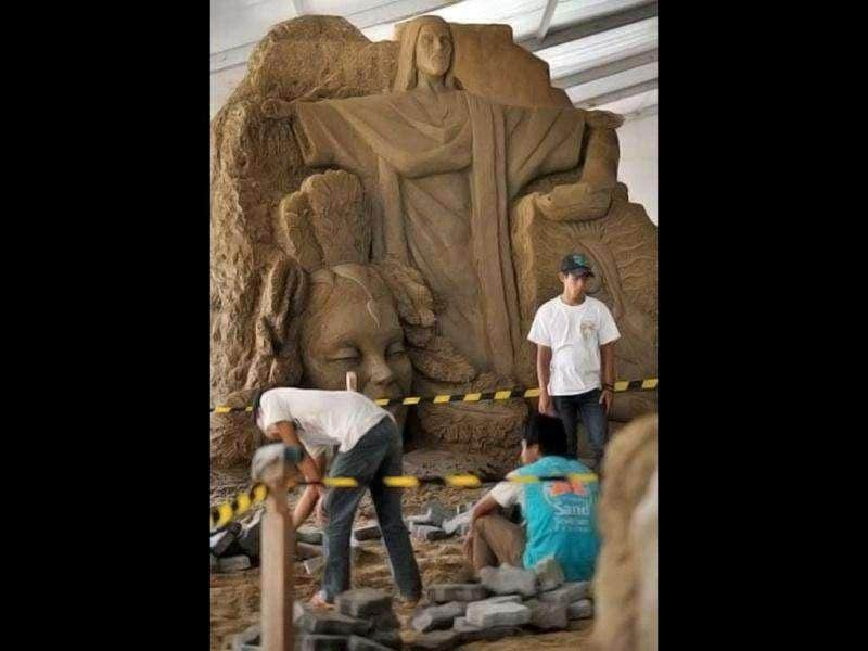 Workers clean the sand sculptures featuring world famous figures and landmarks during the 1st Sand Sculptures Festival at cultural park in Sentul outside of Jakarta, Indonesia. International artists from 11 countries created 40 large sand sculpture pieces of figures and land marks for the first Sand Sculptures Festival. (AFP/Bay Ismoyo)
