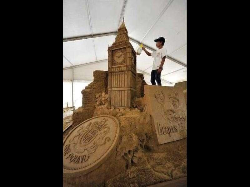 A worker sprays water on sand sculptures featuring world famous landmarks during the 1st Sand Sculptures Festival at cultural park in Sentul outside of Jakarta, Indonesia. International artists from 11 countries created 40 large sand sculpture pieces of figures and land marks for the first Sand Sculptures Festival. (AFP/Bay Ismoyo)