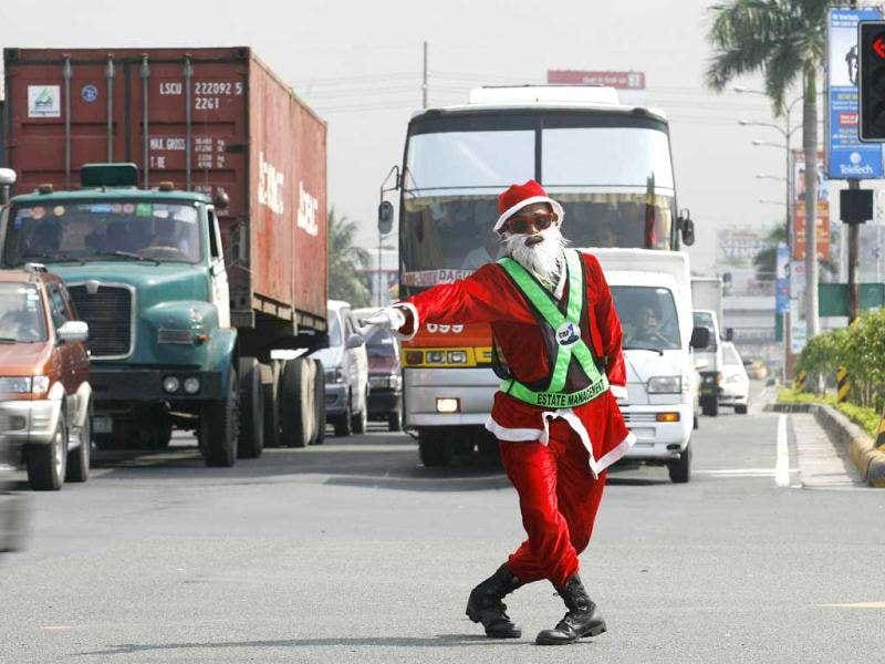 Traffic controller Ramiro Hinojas, wearing a Santa Claus costume, dances as he directs motorists along an intersection in Pasay City, Metro Manila. (Reuters/Cheryl Ravelo)