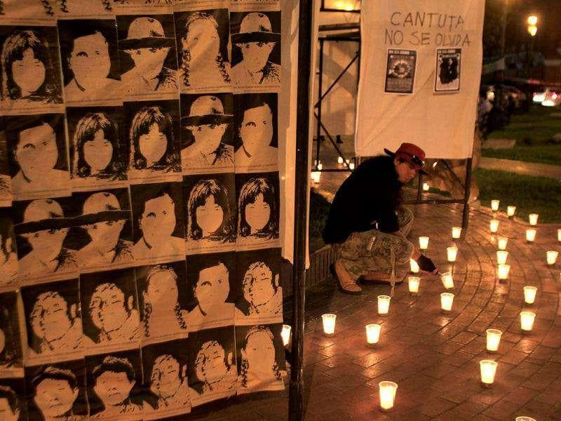 A man lights candles next to a placard with images of people who disappeared during the regime of former Peruvian President Alberto Fujimori, during a demonstration in Lima.