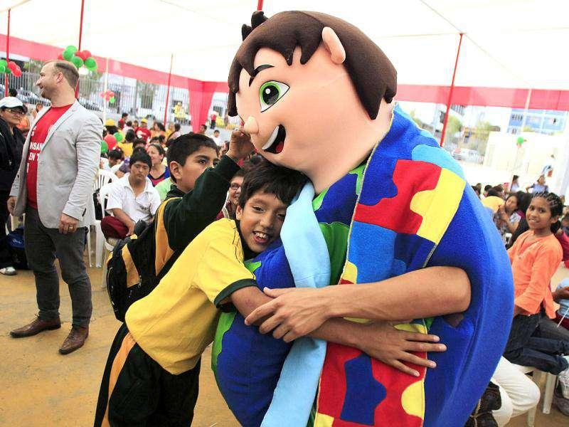 A man wearing a cartoon character costume hugs a disabled boy during a Christmas celebration organised for disabled children by the Ministry of Women and Social Development, in Lima.