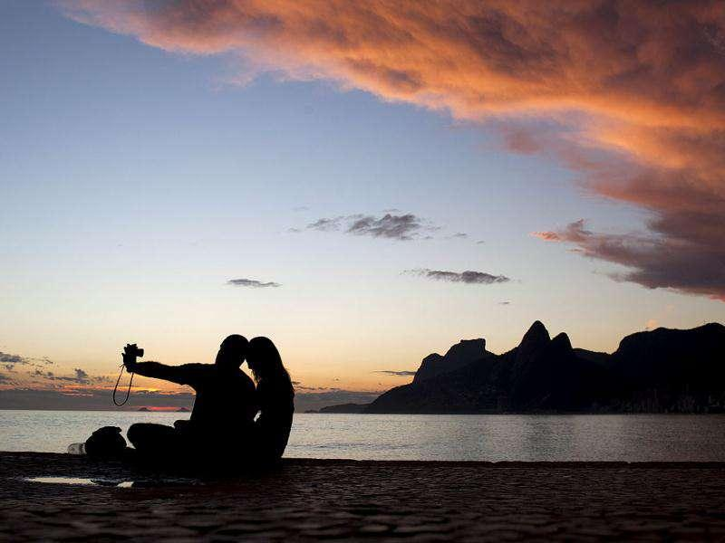 A couple takes a photograph after sunset at the Arpoador beach in Rio de Janeiro, Brazil.