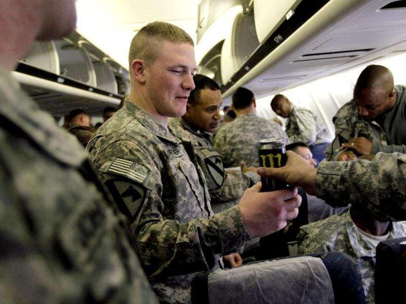 US Army soldiers from the 2-82 Field Artillery, 3rd Brigade, 1st Cavalry Division, drink an energy drink as they wait to disembark from their plane as they arrive at their home base of Fort Hood, Texas after being part of one of the last American combat units to exit from Iraq in Fort Hood, Texas.