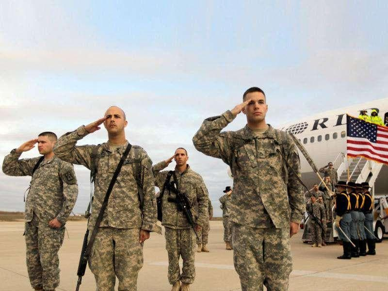 US Army soldiers from the 2-82 Field Artillery, 3rd Brigade, 1st Cavalry Division, salute after walking off the plane as they arrive at their home base of Fort Hood, Texas after being part of one of the last American combat units to exit from Iraq in Fort Hood, Texas.