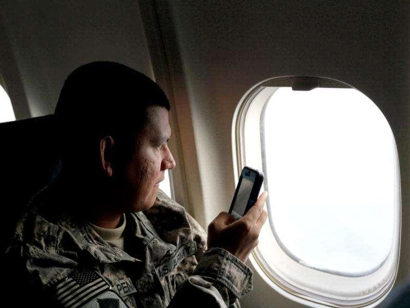 US Army Sergeant Carmelo Pena from LA California of the 2-82 Field Artillery, 3rd Brigade, 1st Cavalry Division, takes a photograph as the plane decends for it landing at their home base of Fort Hood, Texas after being part of one of the last American combat units to exit from Iraq.