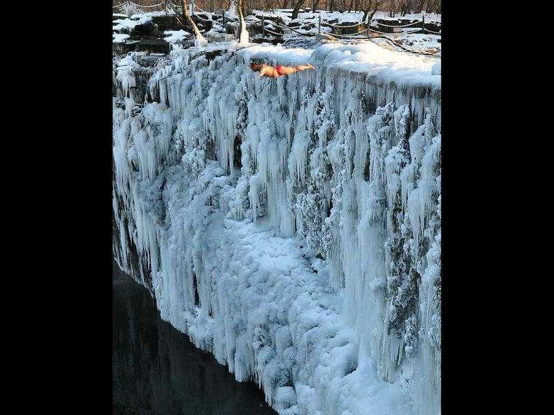 A man diving into the Jingpo lake from a frozen waterfall on Mudanjiang, in northeast China's Heilongjiang province.