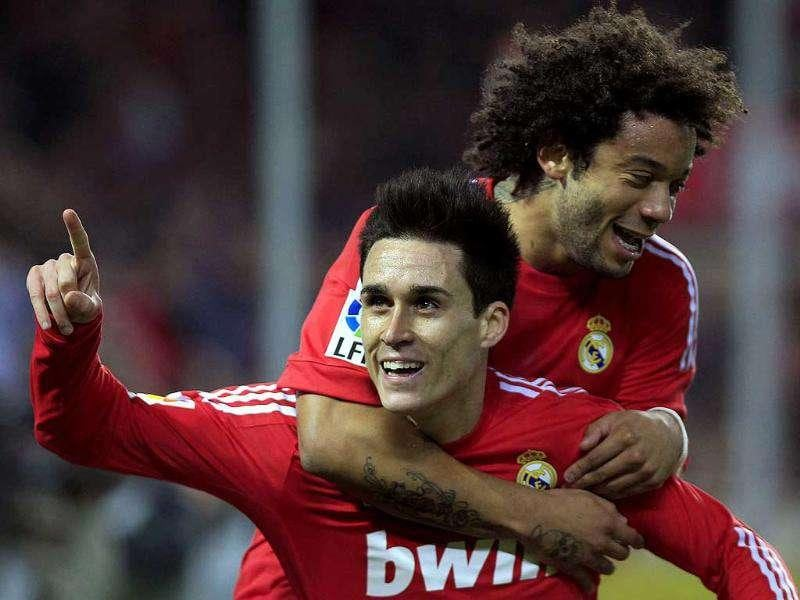 Real Madrid's Jose Callejon, bellow, celebrates after scoring against Sevilla with team mate Marcelo Junior from Brazil, top, during their La Liga soccer match at the Ramon Sanchez Pizjuan stadium in Seville, Spain.