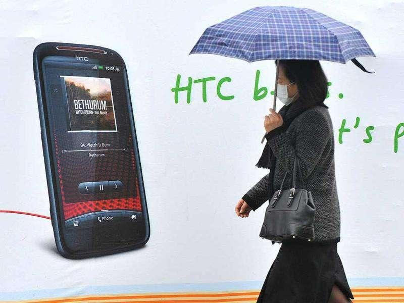 A woman walks past a billboard displaying a handset of Taiwan smartphone maker HTC in Taipei. Apple scored a hit in an ongoing patent brawl with HTC with a US trade authority ruling the iPhone maker has rights to features using one-tap screen commands.