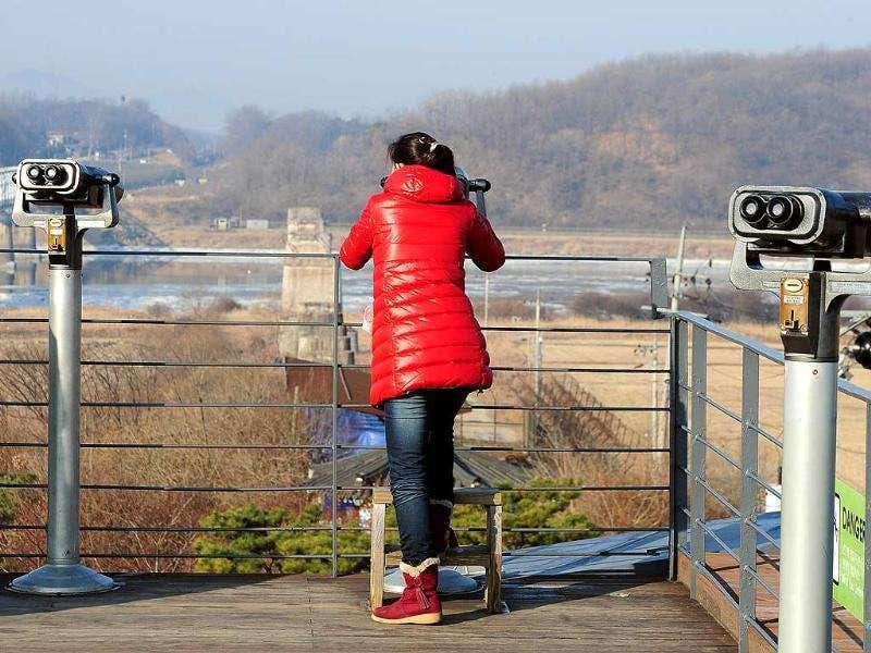 A tourist looks at North side through binoculars at Imjingak peace park in Paju near the Demilitarized Zone (DMZ) dividing the two Koreas.