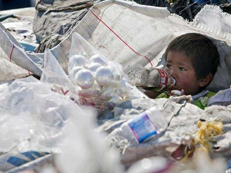 A boy drinks a soda among garbage at the landfill Bordo Poniente on the outskirts of Mexico City. Mexico City will close one of the world's largest dumps by Dec. 31 and will instead turn the garbage from millions of people into reusable materials and energy, Mayor Marcelo Ebrard announced.