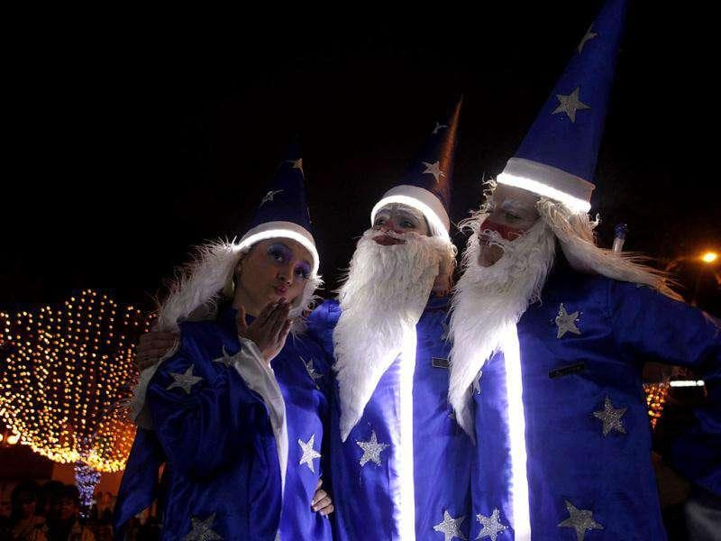 People dressed as Santa Claus are seen at the illuminated Usaquen park in Bogota.