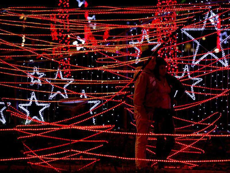 A couple stands in an illuminated park ahead of Christmas in Bogota.