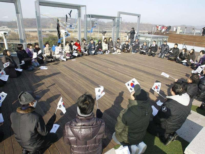 South Koreans hold national flags as they pray for North Koreans from Imjingak near the border village of the Panmunjom (DMZ) that separates the two Koreas since the Korean War, in Paju, north of Seoul, South Korea.
