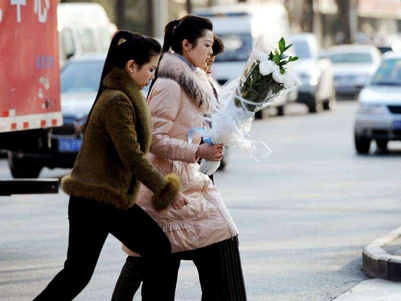 North Korean women holding flowers arrive at the North Korea embassy to mourn the death of North Korean leader Kim Jong-Il in Beijing.