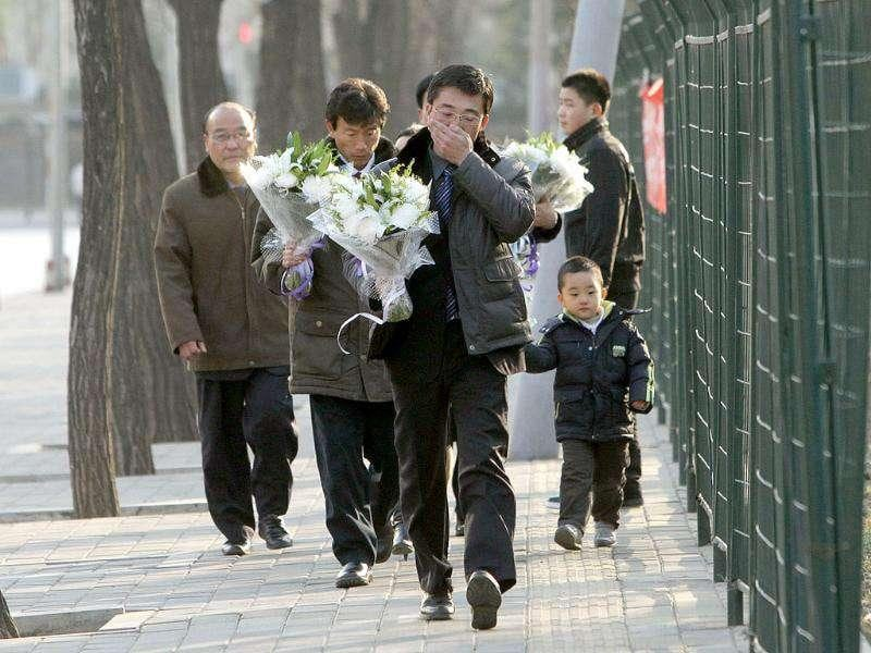 A North Korean man holding flowers grieves as he arrives at the North Korea embassy to mourn the death of North Korean leader Kim Jong-il in Beijing. China's President Hu Jintao visited the North Korean embassy in Beijing to offer his condolences on the death of Kim Jong-Il, the official Xinhua news agency said.