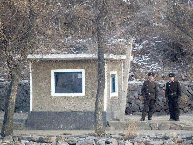North Korean soldiers look as they stand guard along the river bank of the North Korean town of Sinuiju, opposite side to the Chinese border city of Dandong.