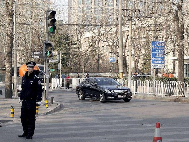 The car believed to contain Chinese President Hu Jintao drives away from the North Korean Embassy, at right, after Hu visited to mourn the death of North Korean leader Kim Jong Il in Beijing, China.