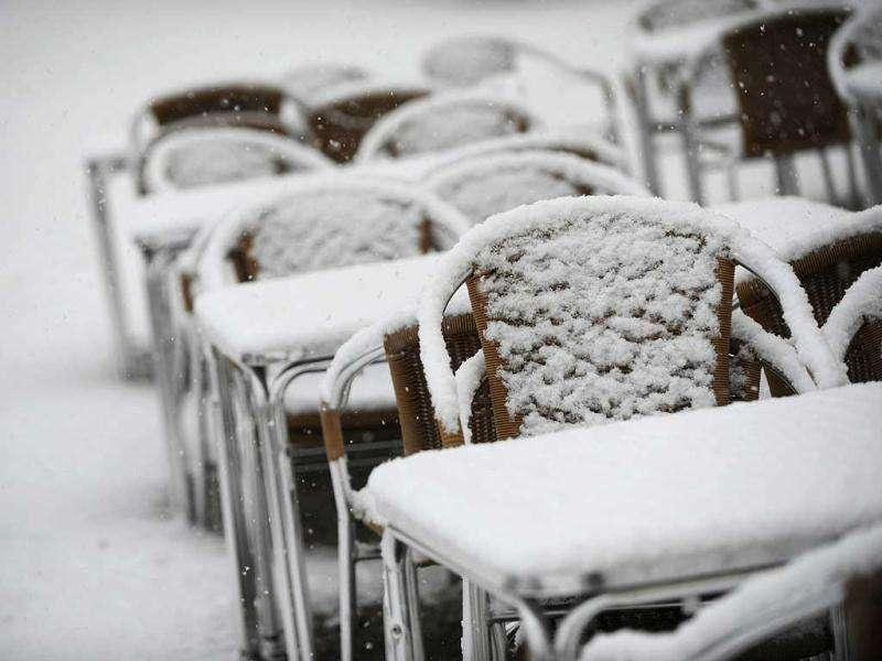 Tables and chairs of a street cafe are covered in snow in Kassel, central Germany. AFP Photo