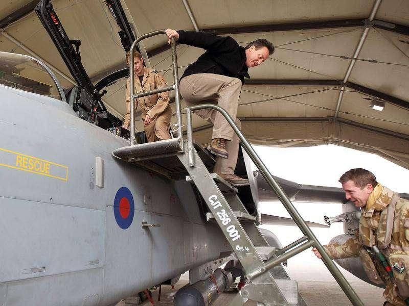 British Prime Minister David Cameron (C) descends a ladder after being shown the cockpit of a Tornado fighter jet by members of the Royal Air Force 12 (B) squadron during a pre-Christmas visit to greet British troops at Kandahar airfield in Kandahar. AFP/Pool/Jeff J Mitchell